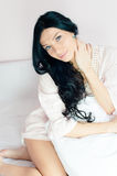 Attractive beautiful young woman sitting in bed Royalty Free Stock Image