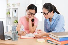 Attractive college student girl doing homework. Attractive beauty college student girl doing school studying homework with individual home teacher feeling bored Stock Photo