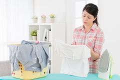 Attractive beauty mother looking at messy clothing. Showing unhappy emotional feeling tired about doing housekeeping standing in front of ironing board Royalty Free Stock Image