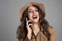 Attractive beauty wearing hat and autumn clothes laughing while talking on the mobile phone Royalty Free Stock Photo
