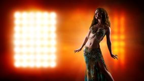 Attractive bellydancer in front of light royalty free stock photo
