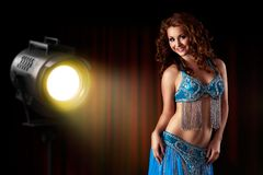 Attractive bellydancer in front of light wall background royalty free stock photo