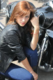 Attractive biker woman and her motorcycle. At the motorbike show Stock Photography