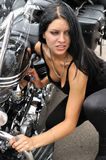 Attractive biker woman and her motorcycle. At the motorbike show,vertical composition Royalty Free Stock Photography