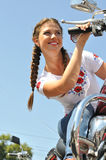 Attractive biker woman sitting on her motorcycle. At the motorbike show Royalty Free Stock Photos