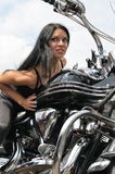 Attractive biker woman sitting on her motorcycle. At the motorbike show Stock Photo