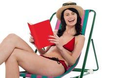 Attractive bikini woman reading a book Stock Photos