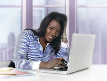 Attractive black African American ethnicity woman working at computer laptop at business district office. Young attractive black African American ethnicity woman Stock Photography