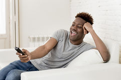 Attractive black african american man sitting at home sofa couch watching television Royalty Free Stock Photos