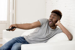 Attractive black african american man sitting at home sofa couch watching television Stock Images