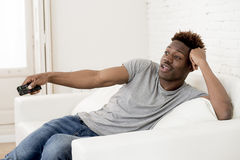 Attractive black african american man sitting at home sofa couch watching television Stock Photo