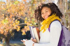 Attractive Black African American Student with Phone. Attractive Black African American Student in Fall with Phone holding books while smiling at camera. Room Royalty Free Stock Photo