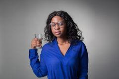 An attractive black African girl in a blue shirt holds a glass of clean water. An attractive black African girl in a blue shirt holds a glass of clean water in royalty free stock photography