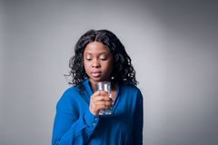 An attractive black African girl in a blue shirt looking down holds a glass of clean water. In her hand royalty free stock photo