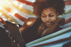 Attractive black cirly girl with digital tablet in hammock. Charming young afro american curly girl enjoying her vacation while laying in striped colourful stock photo