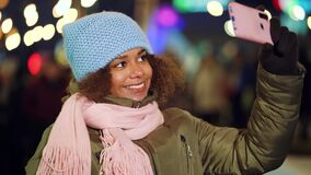 Attractive black girl recording selfie video on Christmas market at night stock footage