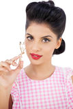 Attractive black hair model holding an eyelash curler Royalty Free Stock Images