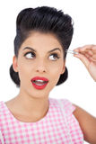 Attractive black hair model using a tweezer Royalty Free Stock Photography