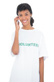 Attractive black haired volunteer calling someone with her mobile phone Royalty Free Stock Image