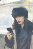 Attractive black haired woman using phone Stock Images