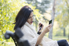Attractive black haired woman using phone Stock Image
