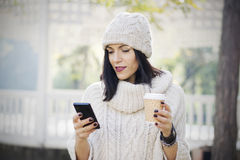 Attractive black haired woman using phone Royalty Free Stock Photos
