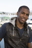 Attractive black male model wearing leather vest at boat marina Royalty Free Stock Photography