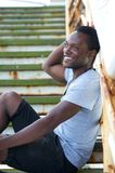 Attractive black male sitting outdoors and smiling Royalty Free Stock Photo
