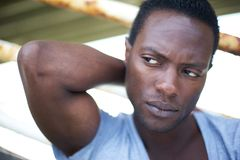 Attractive black man with hand behind head looking away Stock Photos
