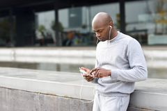 Attractive black man listening to music with headphones in urban. Background. Male in sportswear outdoors stock photos