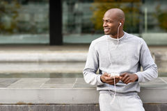 Attractive black man listening to music with headphones in urban Royalty Free Stock Photo