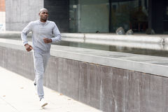 Attractive black man running in urban background Royalty Free Stock Photography