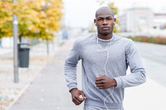 Attractive black man running in urban background Royalty Free Stock Photos