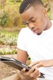 Attractive Black man typing a message on tablet Stock Photos