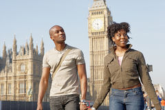 Couple on Westminster Bridge. Attractive black tourist couple holding hands and walking past Big Ben while visiting London city on vacation Royalty Free Stock Image