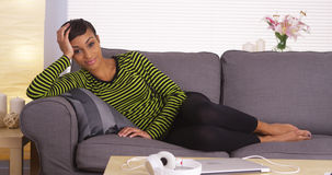 Attractive black woman lying on couch looking at camera Stock Images