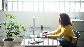 Attractive black woman works on computer in office