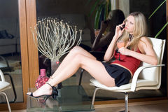 Attractive blond. Woman with a glass of cocktail speaking on the phone stock images
