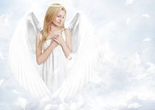 Attractive blond angel in sky. Attractive blond haired angled in sky with decorative blue and white background royalty free stock image