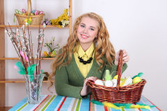 Attractive blond, basket with easter eggs and pussy-willow. Indoor Royalty Free Stock Photography
