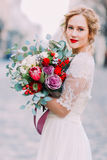 Attractive blond bride with huge bouquet of roses and peonies looks into the camera Royalty Free Stock Images