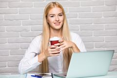 Attractive blond business woman working on her laptop and drinking coffee in her office Royalty Free Stock Photography