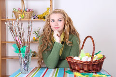 Attractive blond with easter eggs in basket Royalty Free Stock Images