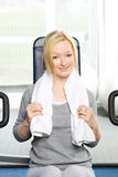Attractive blond exercising in gym. Young attractive blond girl exercising at the gym Stock Image