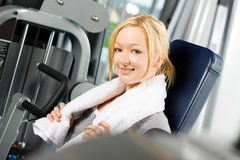 Attractive blond exercising in gym. Young attractive blond girl exercising at the gym Stock Photography