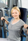Attractive blond exercising in gym Stock Photos