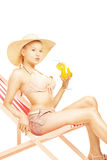 Attractive blond female with hat sitting on a sun lounger and dr. Inking a cocktail, isolated on white background Stock Photo