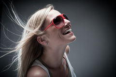 Blond woman model  laughing. Attractive blond female model laughing while posing on a gray background Stock Photos
