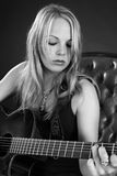 Attractive blond female playing guitar royalty free stock photography