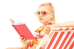 Attractive blond female sitting on a sun lounger and reading a b Royalty Free Stock Photography